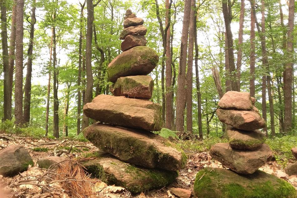 2 Steinpyramiden im Wald, eine größere mittig, rechts eine kleinere