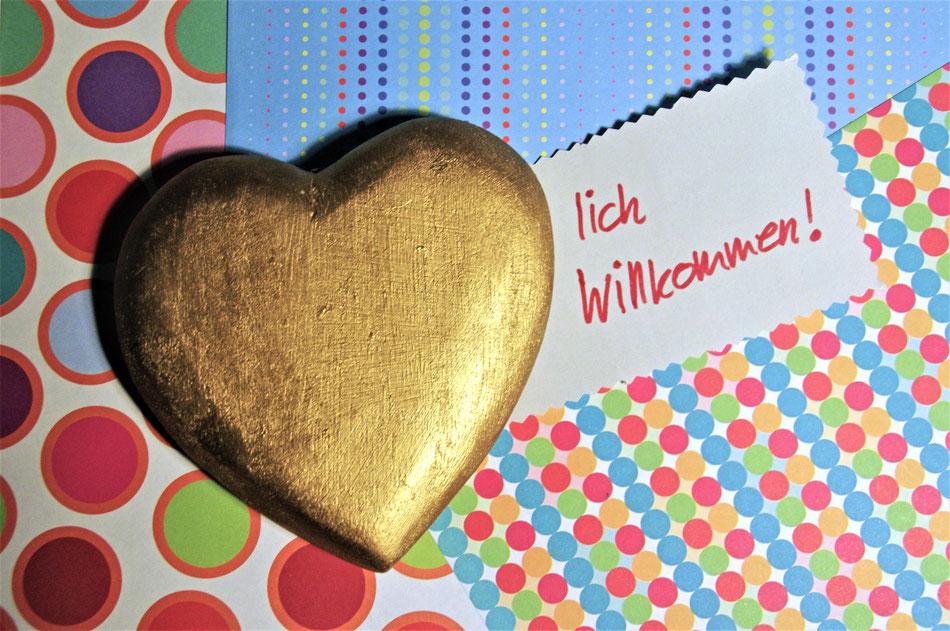 """goldenes Herz auf bunt gemustertetem Untergrund. Neben dem Herz Schrift """"lich Willkommen!"""""""