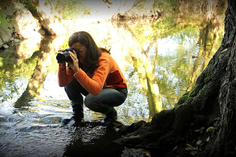 Sybille hockt mit Gummistiefeln in einem Bach und fotografiert