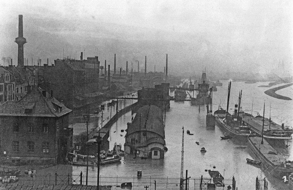 Der Mülheimer Hafen bei Hochwasser: vorne links liegt das Hafenamtsgebäude, dahinter die Syberberg-Mühle an der Hafenstraße, im Mittelgrund zahlreiche Schlote der Industrie, beginnend mit Lindgens & Söhne, rechts die Hafeneinfahrt mit der Rheinmole.