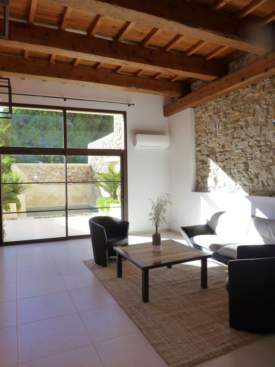 Un grand salon d'environ 50m² est à votre disposition, avec vue sur le patio