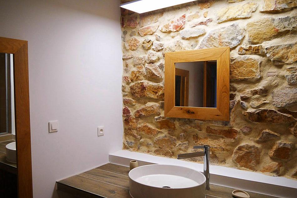La salle de bains rappelle l'authenticité de la région, avec ses matériaux bruts (chêne et pierres). Baignoire-douche supérieure aux standards