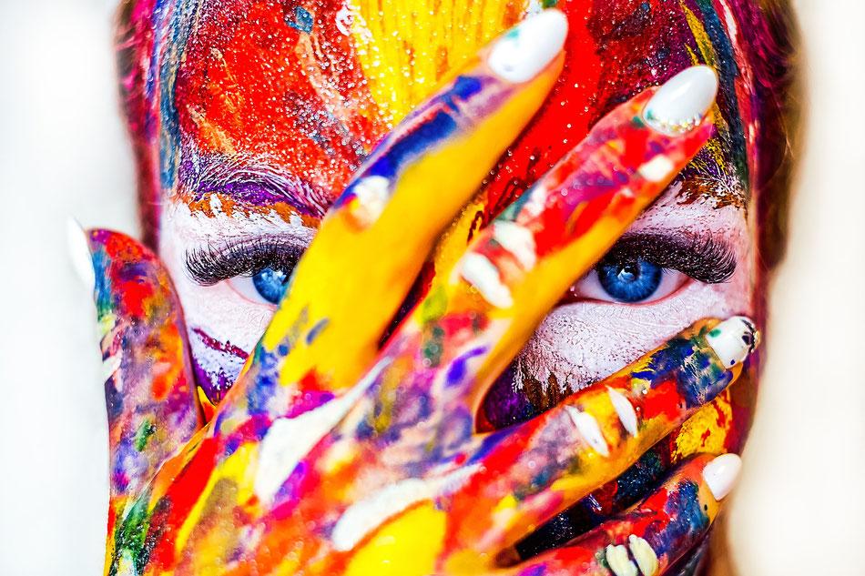 Ragazza con il viso colorato di vernice che si copre il volto