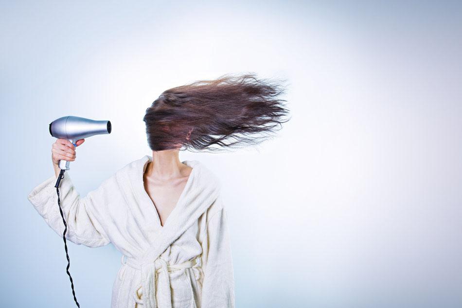 Ragazza che usa il phon e viene coperta dai suoi capelli
