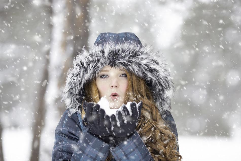 Ragazza che soffia la neve dalle mani