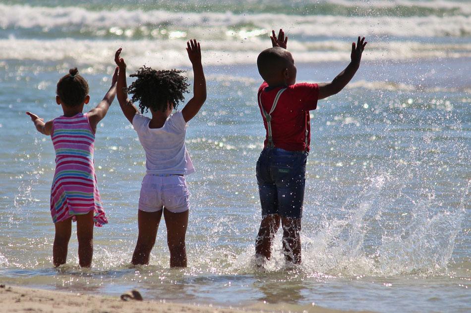 Bambini che giocano con l'acqua del mare