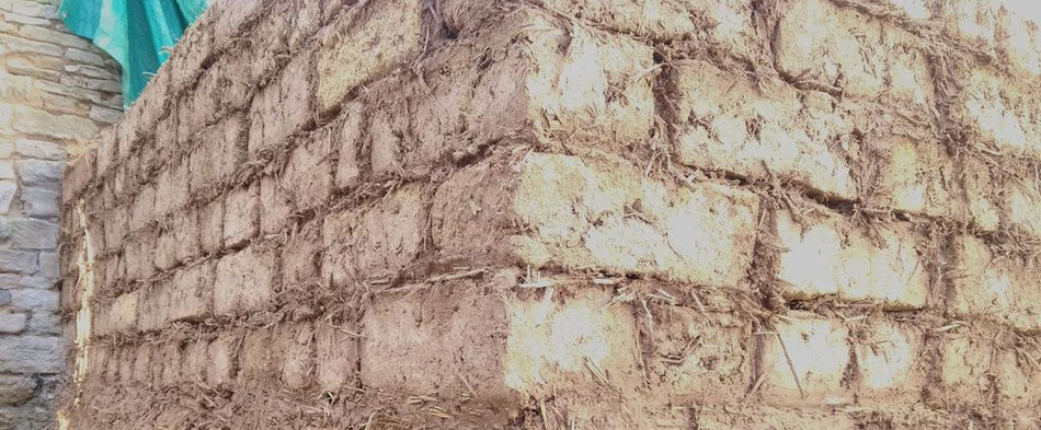 Montage d'un mur d'adobes hourdé avec un mortier terre paille