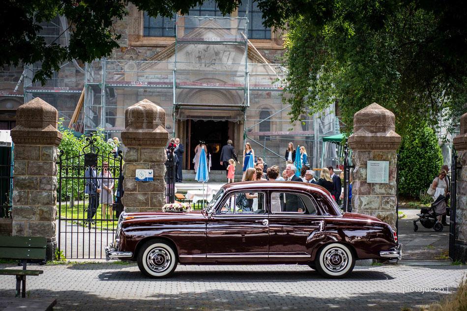hochzeitsauto steht vor der evangelischen peterskirche in Weinheim