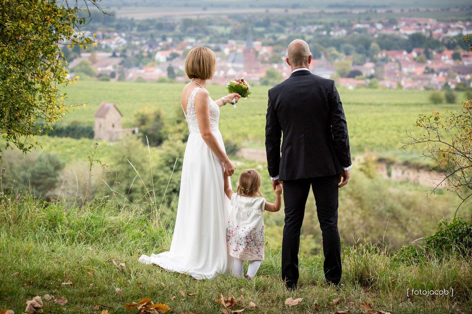 brautpaar mit kind von hinten blickt ueber Deidesheim in der pfalz
