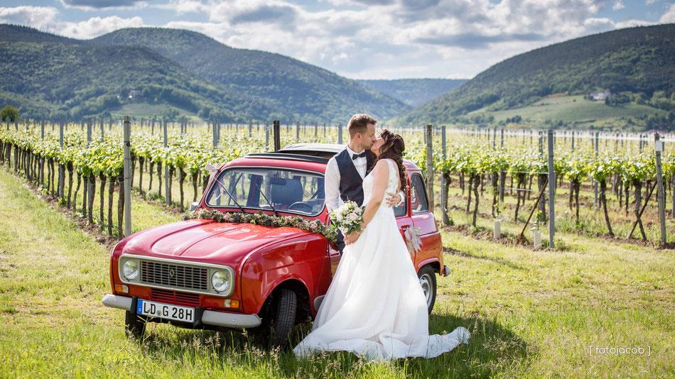 brautpaar mit rotem auto im weinberg pfalz