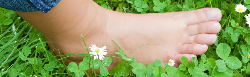 Gesunder unbekleideter Fuß in Blumenwiese