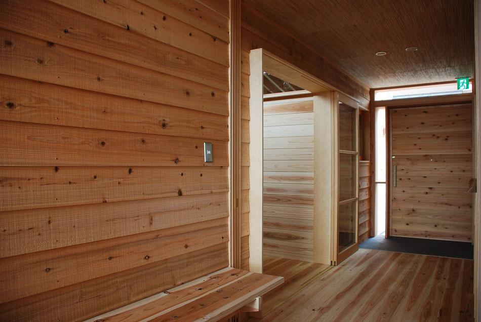 廊下から玄関側をみる。  手前の引き戸は壁内に収納できるようにしている。