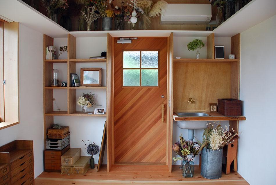 玄関戸と収納棚。  こだわりのアイテムがところ狭しとディスプレイされている。  インテリアと建物に統一感がある。