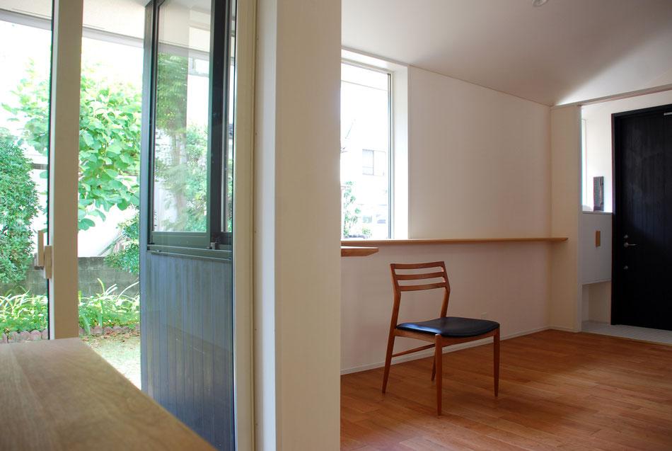 寝室から玄関側を見る。窓外に緑が広がっている。2つの窓下に沿ってL型のカウンターが玄関へと伸び、手持ちの小物を飾ることができるようにしている。