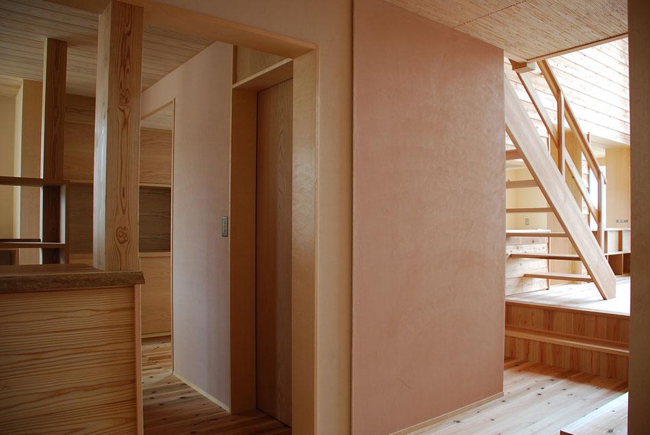 内部は共用トイレ。  2色の漆喰の塗り分けを、細く突き出た建具の戸当りで納める。  様々な素材が見え隠れしている。