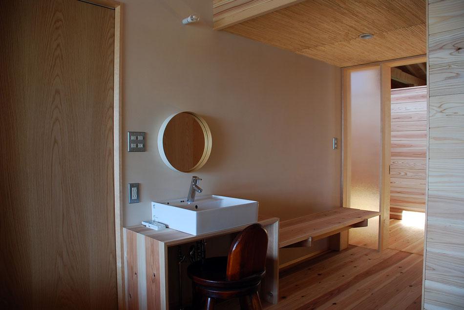 宿泊室内洗面台。洗面台右手には片持ちのベンチ。  さらにその右手に廊下との間の型板ガラスを嵌めており、廊下の様子・室内の様子が互いにそれとなく感じられるようになっている。