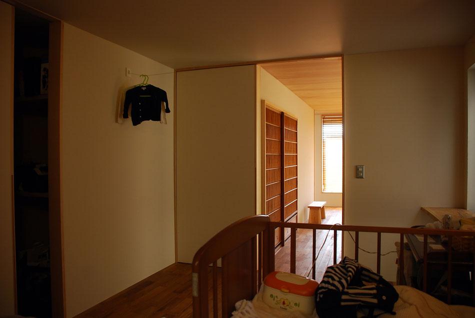 寝室の引戸は塗装仕上げとし、塗り壁の色に揃えている。  室内干しできるよう、壁にはワイヤーを張っている。