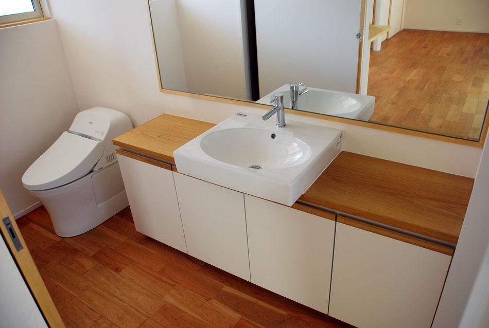 一人暮らしの住宅なので、洗面室内にトイレを設けている。大きな鏡を取付けて小さな空間を広く見せている。