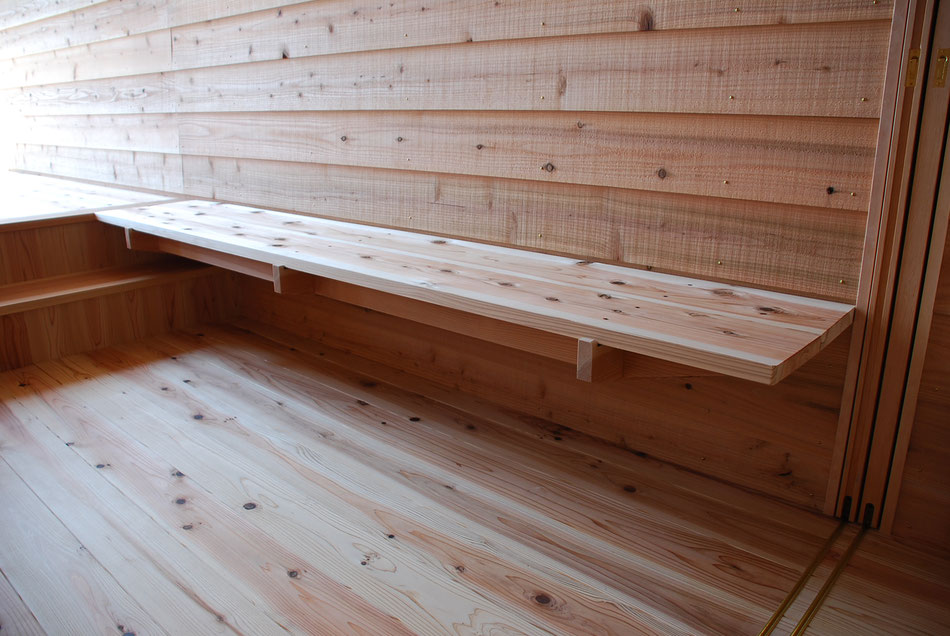 杉板のベンチ。中央に向かって少し傾斜を付けて、座りやすい形状にしている。  壁の木板は、鋸引き仕上げとし、素材感を出している。