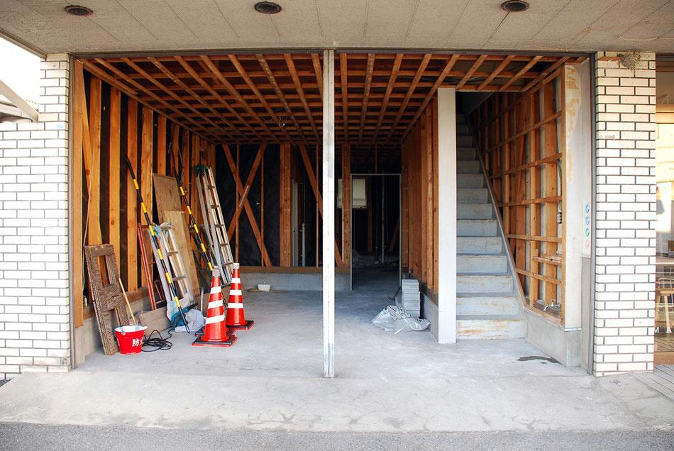 車庫兼倉庫部分の解体着手時の様子。  床は土間仕上げであったが、束立てして床組みをし、50cm程床を上げている。  柱梁に構造金物を新たに設置し、改修と同時に耐震補強も行った。  この段階では階段横にまだ事務所に通じる開口は開いていないのが分かる。