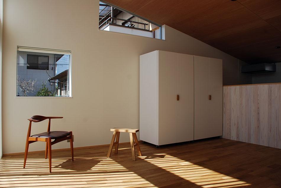 リビングダイニング。  勾配天井によって南側は最大で3.5m程の天井高さ。  西側壁にはシャープな枠廻りの窓が2つあり、見える景色が際立っている。  左側の窓は、片引き窓になるよう納まりを工夫をしている。