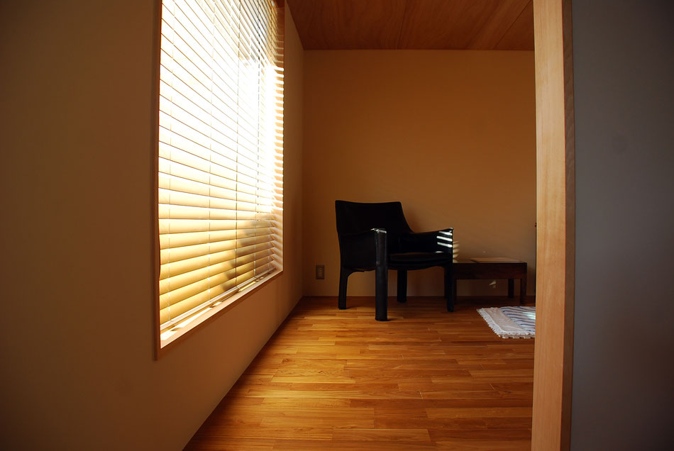 ベージュ色の塗り壁にチークのフローリング、天井は合板仕上げ。