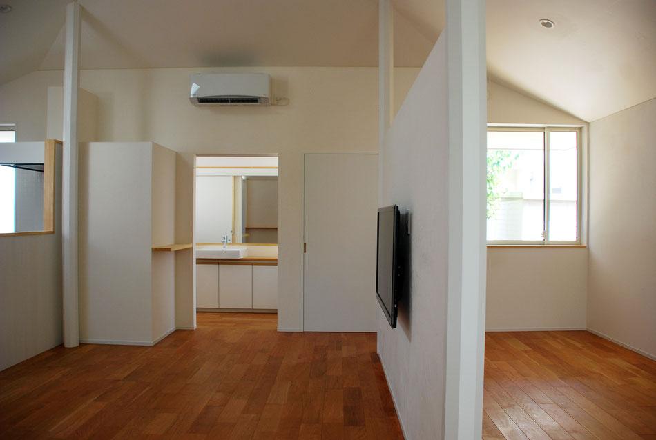 左手のキッチン換気扇から右手の間仕切りまで、全てを1.8m高で統一し、全体の視点や重心を下げている。中央奥は洗面室。