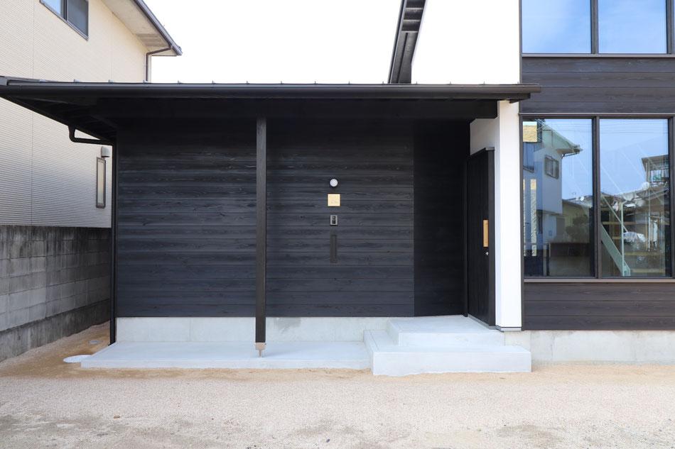 東側アプローチの様子。下屋の軒の出を大きくし、玄関廻りに雨除けスペースを大きく確保している。