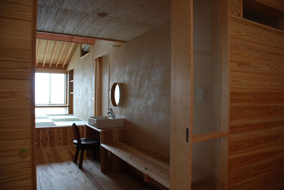 宿泊室内をみる。  漆喰壁に反射する光によって、左官仕上げの手仕事感が伝わってくる。  畳敷き部分は一段高くしている。