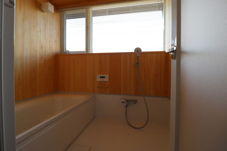 ハーフバスの浴室。腰上は桧板張りに大きな窓を設置