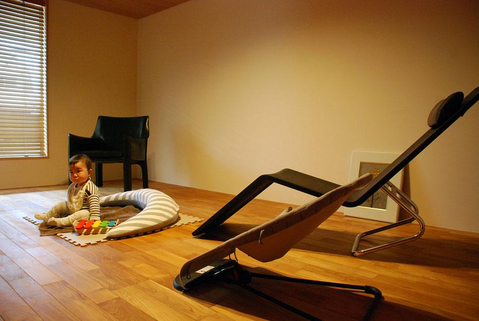 トーンを落とした色調に、黒の家具が映えている。  左官仕上げの壁にダウンライトの光が柔らかく注いでいる。