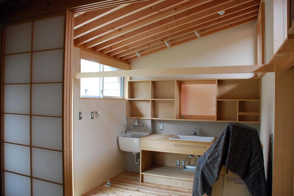 分娩室内の水廻り。カーテンで仕切ることができる。  棚中央には開閉できる小窓があり、玄関を通る人の気配を感じることができる。