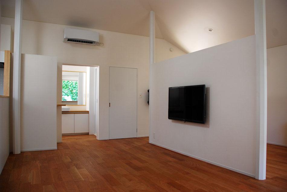 内部中央はダイニング。右手の寝室とは1.8m高の間仕切り壁によって緩やかに分けている。