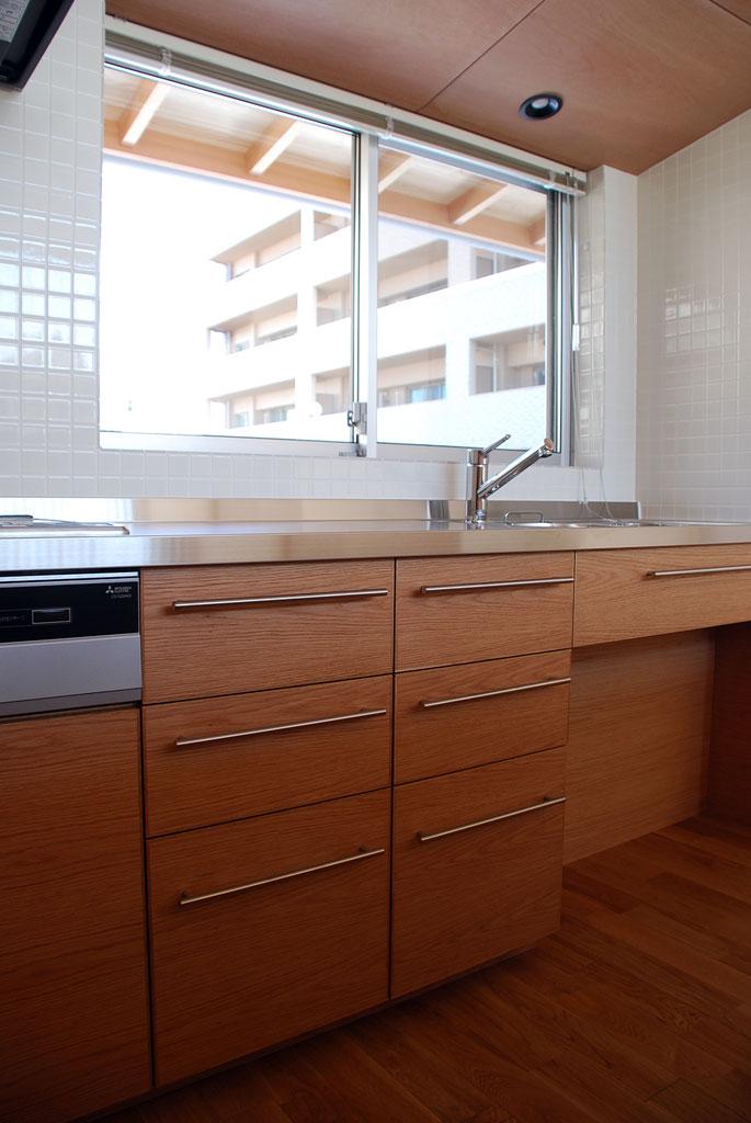窓越しに軒裏が見える。  サッシのクレセントは低くし、ブラインドを下ろしても操作しやすい位置とする。  キッチン引出の鏡板は、左右で木目が連続するようにしている。