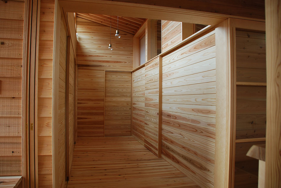 宿泊室と分娩室に向かう際に通る廊下。  建物中央部で暗くなりがちな場所であるが、ハイサイドライトによって北側にも光が落ちるようにしている。  壁仕上げは全て杉板。建具も同様の仕上げに揃えている。