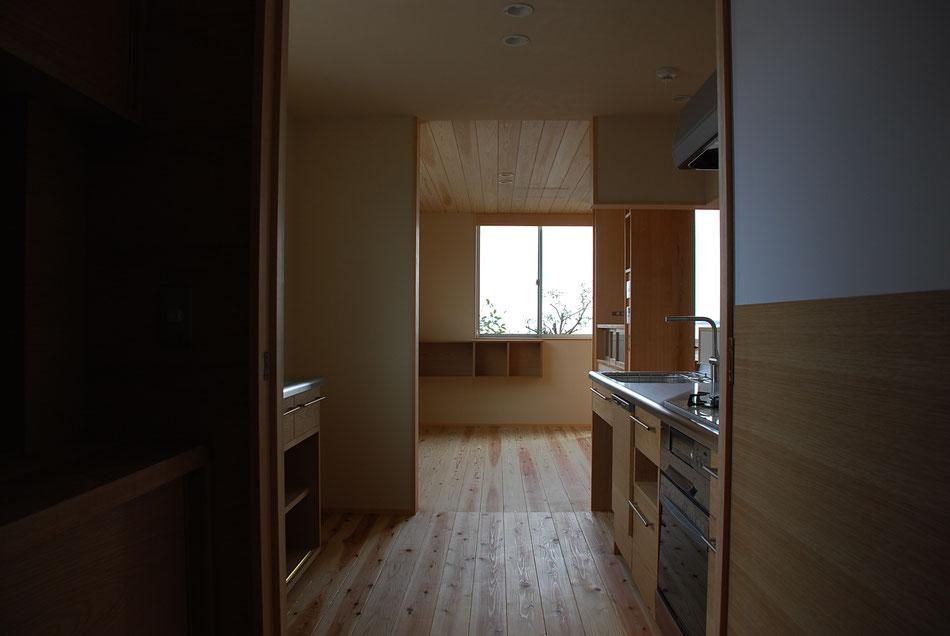 キッチンの向こう側にダイニング。  キッチンキャビネットは製作とし、他の家具と面材を統一。  手前右側にあるのは開き戸。上半分はマグネット機能付きホワイトボード貼り。