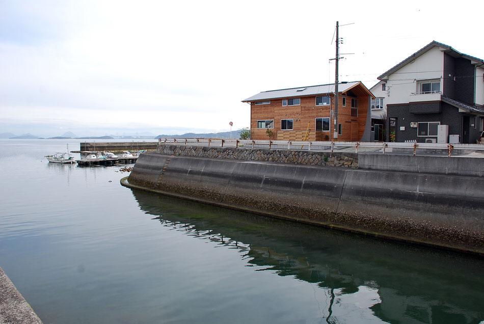 水路対岸から望む。助産院は海を向き、遠く瀬戸大橋や四国が広がる。