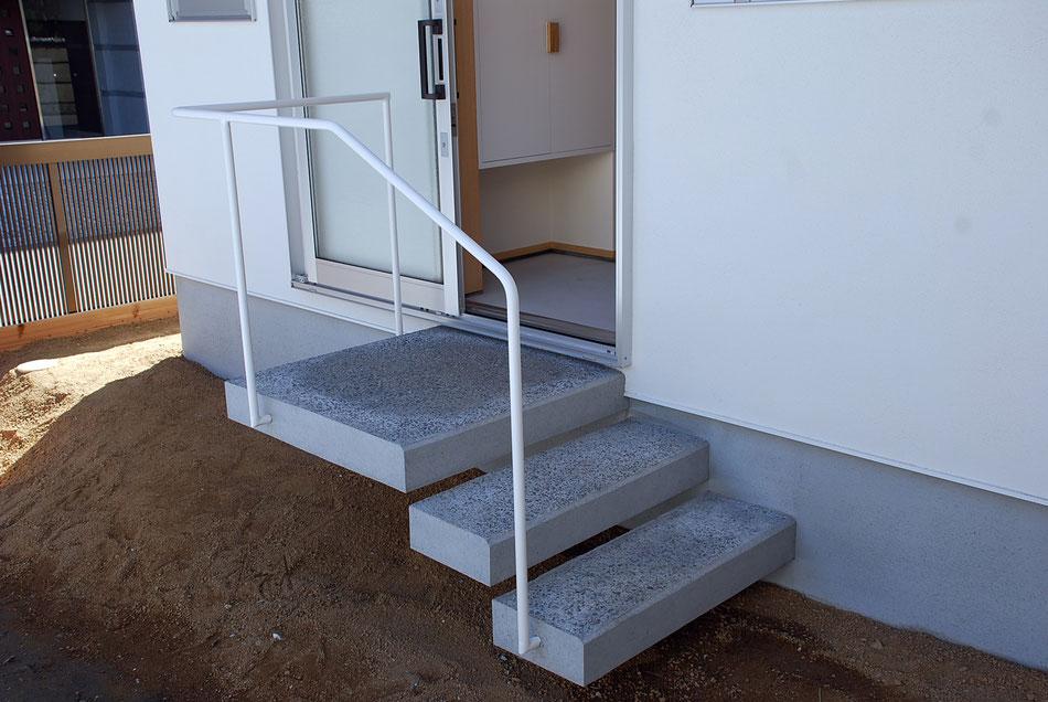 階段踏面のみ粗面にし、意匠性と滑り止めの役割を果たす。  一方、玄関土間は平滑に仕上げ、清掃しやすいようにしている。