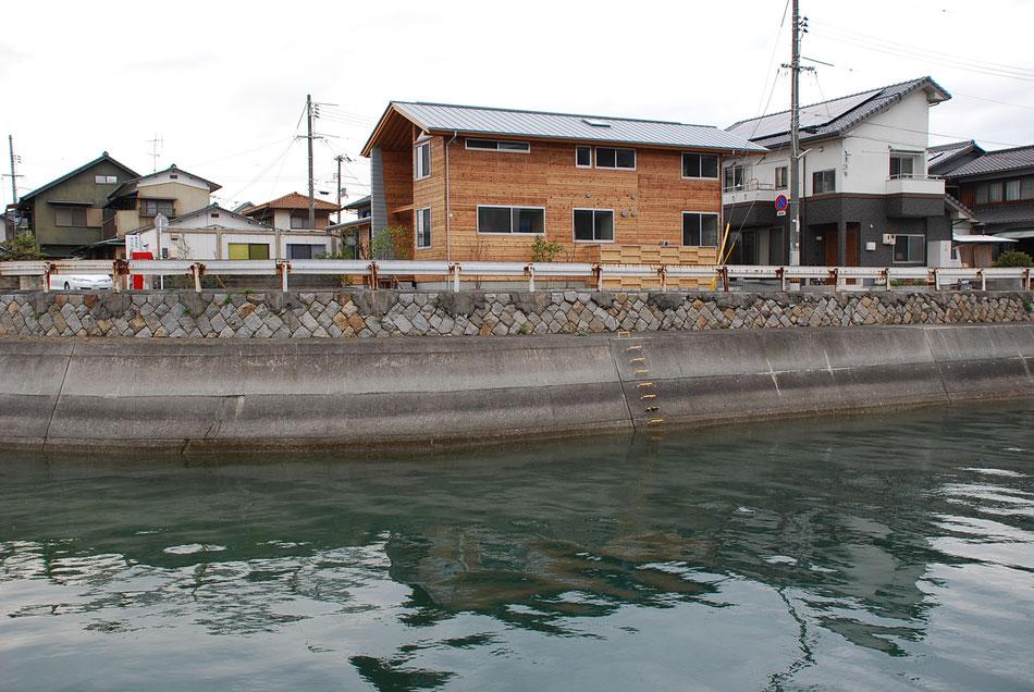 水路越しに助産院をみる。水面の輝きに呼応させた形で屋根板金色を選ぶ。