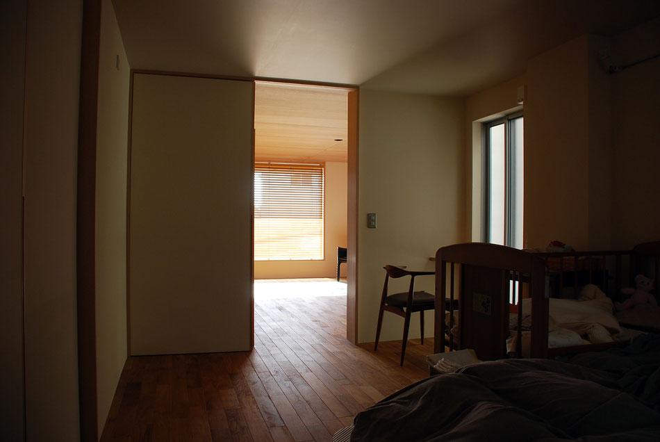 2室が連続するよう、引戸は吊りとし、フローリングが連続している。  右手の窓前には作り付けのカウンターがあり、アイロン台として活用している。