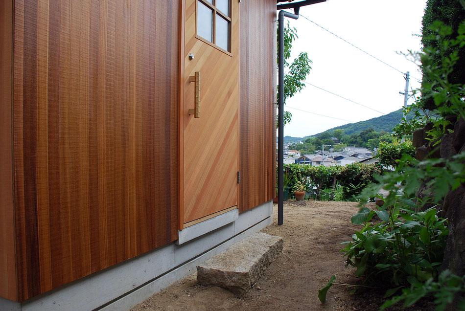 玄関前には沓脱石。  外壁木板と同材を、玄関戸に斜め張り。  特注のクリの引手。