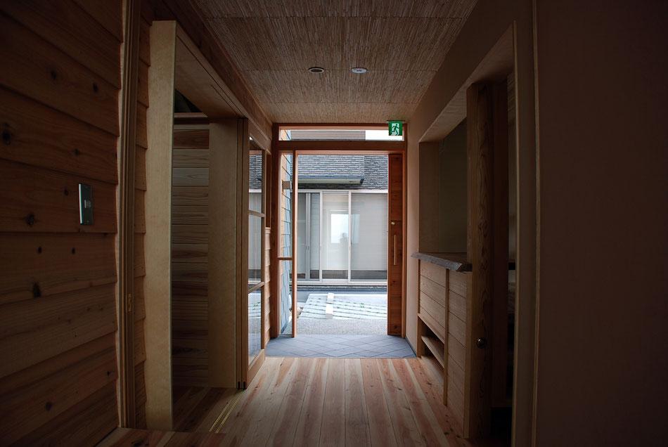玄関見返し。救急搬送の台車やベビーカーの使用を想定し、玄関土間とフロアはフラットにしている。  素材の違いのみで靴脱ぎ場を示す。