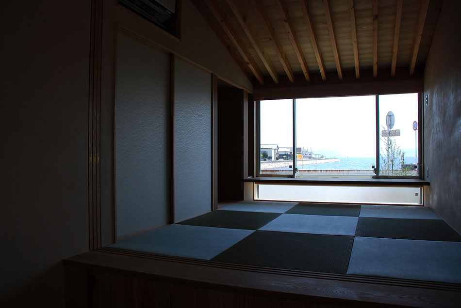 宿泊室の畳敷き。窓の外には海が広がる。  窓辺にはカウンター天板を設え、また足元を掘り込み、足を下ろすことができるようになっている。  襖の左手には3連の障子を収納しており、必要に応じて宿泊室内を間仕切ることができる。