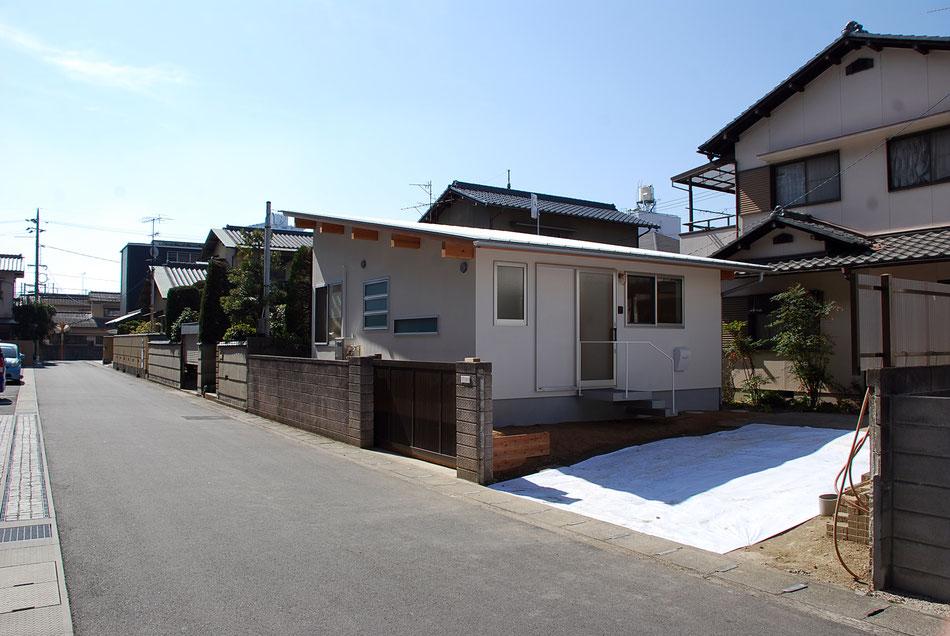 アプローチとなる北東側からの眺め。  敷地区画が比較的広い宅地が続く岡山の中でも落ち着いた住宅街。  母屋の手前にあった駐車エリアに新しく建物を配置している。