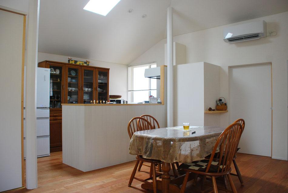 ダイニング越しにキッチンを見る。キッチンの手元を隠すように羽目板張りを高くしている。中央右手の矩形は洗面室側にある洗濯機置き場の外形。