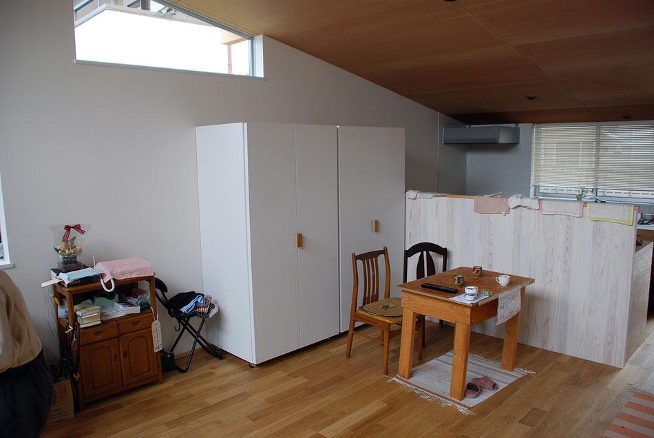 大型の可動収納が2つあり、夫妻それぞれのクローゼットとなっている。  右手奥はキッチンがあり、キッチンの雑多な様子が見えないよう、衝立の高さを設定している。