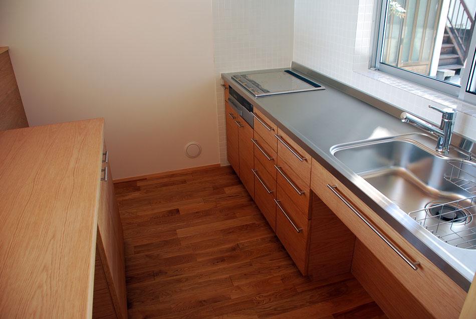 キッチンキャビネット天板はステンレス仕上。  左側の背面キャビネット天板は木板仕上としている。左奥は冷蔵庫置場。