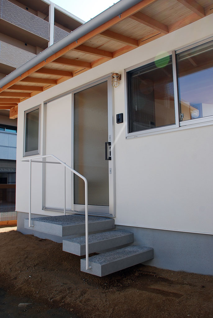 低く伸びた軒下空間に、軽やかな片持ち階段が3段。  玄関戸は簡素な片引戸を設える。  垂木間の面戸板に通気スリットを切る。