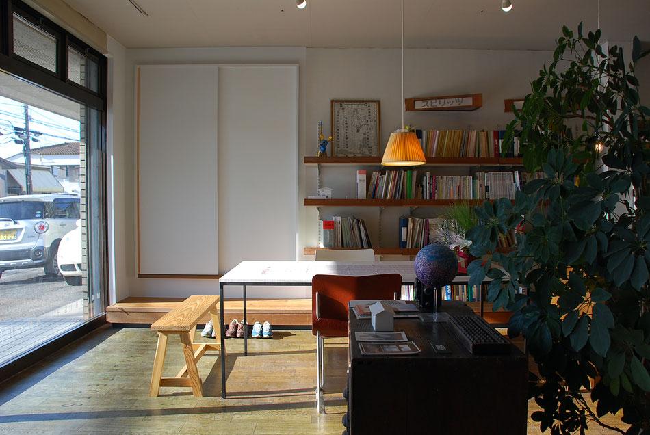 事務所内部の様子。左の引戸が住居側への入口。  特注の打合せテーブルは極細のスチール製フレーム。