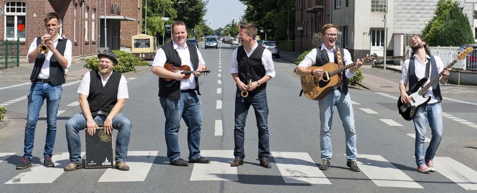 6 Männer mit Instrumenten stehen auf einem Zebrastreifen auf einer Straße und lachen.